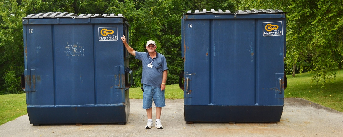 Photo of employee with recycling bins