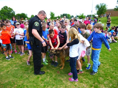 Group of children pet a K-9 dog.